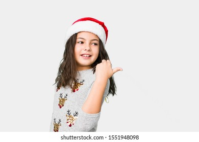 Little girl celebrating christmas day points with thumb finger away, laughing and carefree.