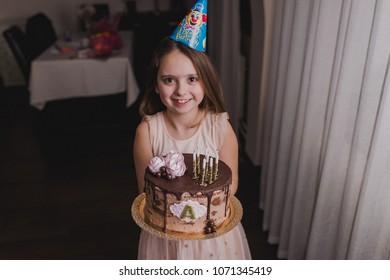 Little girl celebrating her birthday, holding a cake