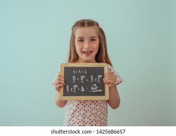 little girl with chalkboard calculating
