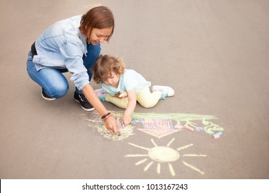 Little girl chalking at the asphalt with elder sister or nanny.  Best friends children, happy family. Drawing with color chalk.
