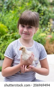 little girl with a little chicken in his hands