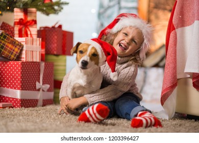 Little girl child celebrating a happy Christmas at home by the fireplace with a pet dog Jack Russell