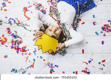 Little girl child cute and beautiful with multi-colored confetti on the floor happy is happy in a paper crown  Princess
