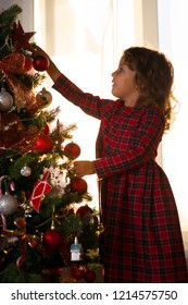 Little girl child decorate a Christmas tree against the window with a setting sun and bright sunlight