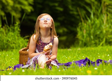 Little girl child eating sandwich hot dog on picnic. Summer vacation leisure. Happy kid relaxing in park meadow.