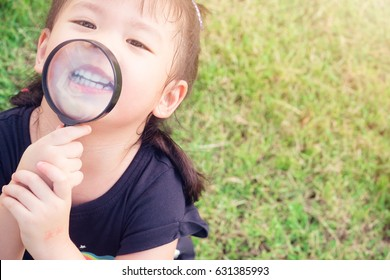 Little girl child holding magnifying glass and showing front teeth with big smile on green grass: Healthy happy funny smiling face young adorable lovely female kid with new tooth dental loss.