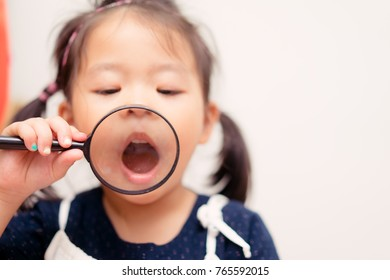 Little girl child holding magnifying glass and showing front teeth with big smile on white background: Healthy happy funny smiling face young adorable lovely female kid with new tooth dental loss.