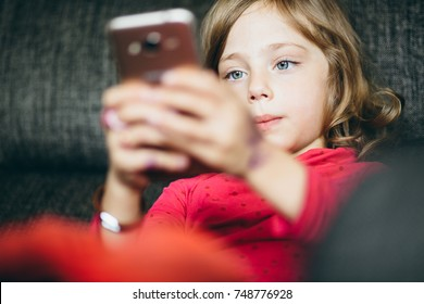 Little girl child kid using phone tablet computer playing games