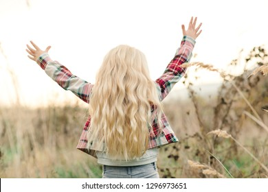 Little girl child with long blondy wavy hair. Happy child raise up hands at sunset at nature. Beautiful warm summer evening. Kids fashion. Happy childhood. Dream and freedom concept. Healthy hair