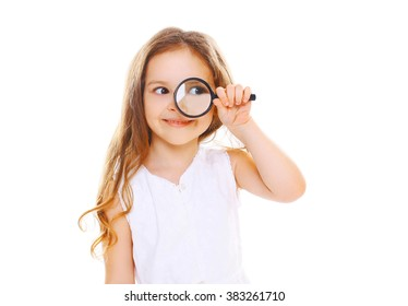 Little girl child looking through a magnifying glass on white background