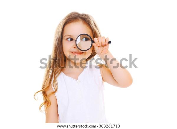 Kleines Mädchen, das durch eine Lupe auf weißem Hintergrund schaut