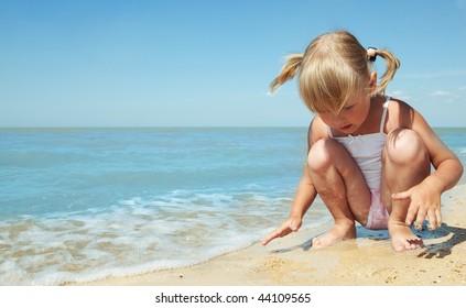 little girl child on the sea under blue sky