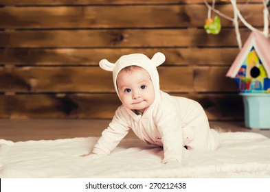 little girl. child in pink overalls with ears.crawling on the background of wooden planks