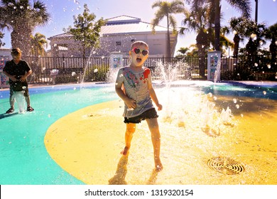 A little girl child is playing in the water fountains at a splash park playground on a summer day.