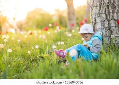 little girl child plays on the smartphone leg to the leg in a field with green grass and blooming tulips
