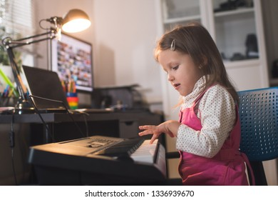 little girl child plays piano synthesizer at home in her room
