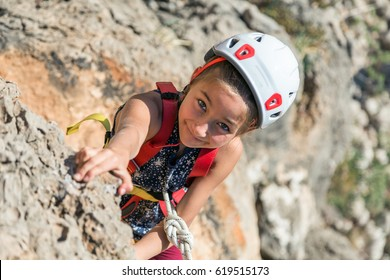 Little Girl Child in protective Helmet training Rock climbing on natural outdoor Wall with belay Rope fixed to Harness