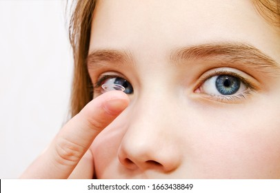 Little girl child putting contact lens into her eye closeup