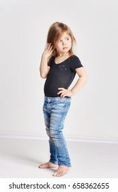 Little girl child with red hair, beautiful long hair. Joy and fun. Posing on a light background, fashion model school