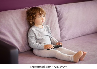 Little girl child with remote control watching tv set in room.