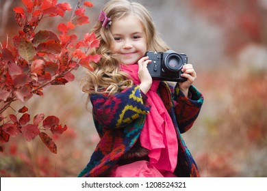 little girl child with retro camera in red autumn forest. beautiful nature outdoors. little photographer