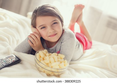 Little girl child with snacks and remote control watching tv set lying on bed in room. 6 years old child watching tv laying down on a white carpet at home alone. cute little girl
