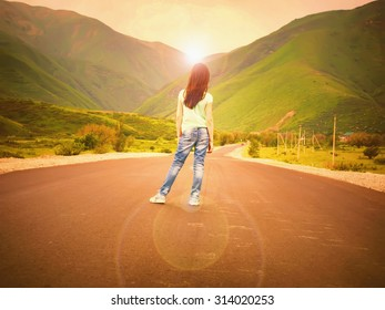 Little girl child walking on road to mountains at sunset outdoor