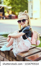 Little girl child wearing a sunglasses and backpack standing in over city background