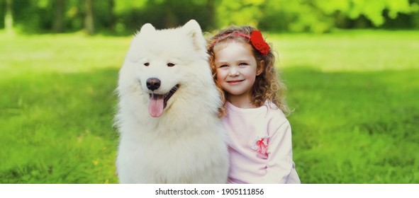 Little girl child and white samoyed dog together on a grass in summer park