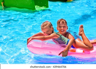 Little girl children swiming on pink inflatable beach mattress at swimming pool.