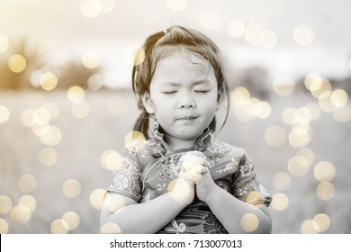 Little girl in chinese dress traditional cheongsam praying in the morning.Little asian girl hand praying,Hands folded in prayer concept for faith,spirituality and religion.Sepia tone.Vintage tone.