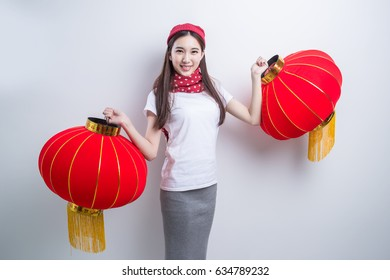"little girl in chinese traditional dress with lantern with many ""luck"" on it."