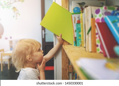 little girl choosing and taking book from shelf to read