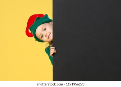 Little girl in a Christmas elf costume on a yellow background. A child looks out from behind a black sheet. Festive photo with place for text, copy space.