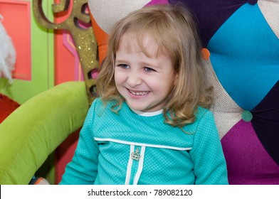 Little girl at Christmas is playing in the mall. The child sits on an armchair with toy snowmen, examines gifts near the Christmas tree.