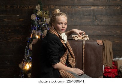 Little girl with a Christmas present on wooden background. Christmas story concept. Christmas teenager homeless. Christmas unhappy children