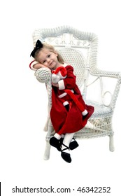 Little girl with Christmas red dress on holds her Santa Claus doll and rests her head on her arms.  Wicker chair in all white room.