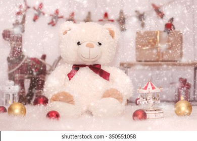 Little girl in christmas setting wearing long red and white woolen hat with big gift boxes and toy rain deer