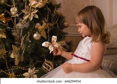 Little girl with a Christmas toy near a festive Christmas tree