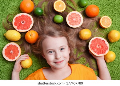 Little girl with citrus fruit smiling on the grass. Vitamins