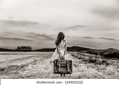 Little girl in classic dress with travel suitcase at autumn wheat field. Tourist concept image . Image in black and white color style