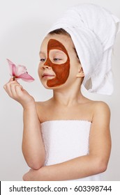 Little Girl with a clay mask on her face