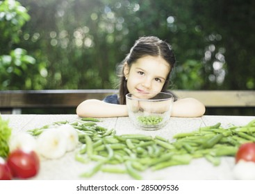 Little girl cleaning peas and recommend you to eat healthy food