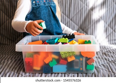Little girl cleaning up the toy box at home. Child's space organization.