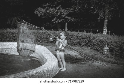 Little girl cleans the pool from the leaves