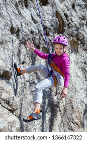 Little girl climbing on  rock in mountains