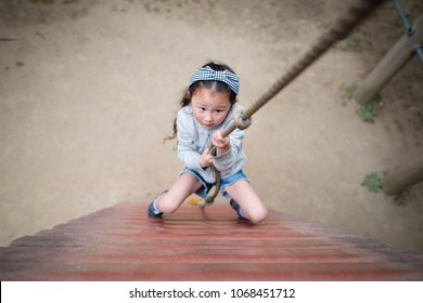 Little girl climbing on the rope