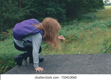 little girl climbing onto a platform whilst out on a hike walk