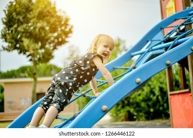 little girl is climbing and playing at the playground