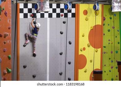 little girl climbing a rock wall